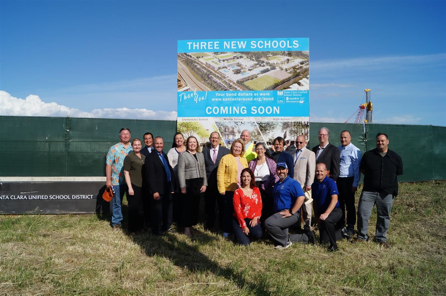 Board of Trustees, superintendents, bond projects and public relations staff pose in front of Agnews construction signage.