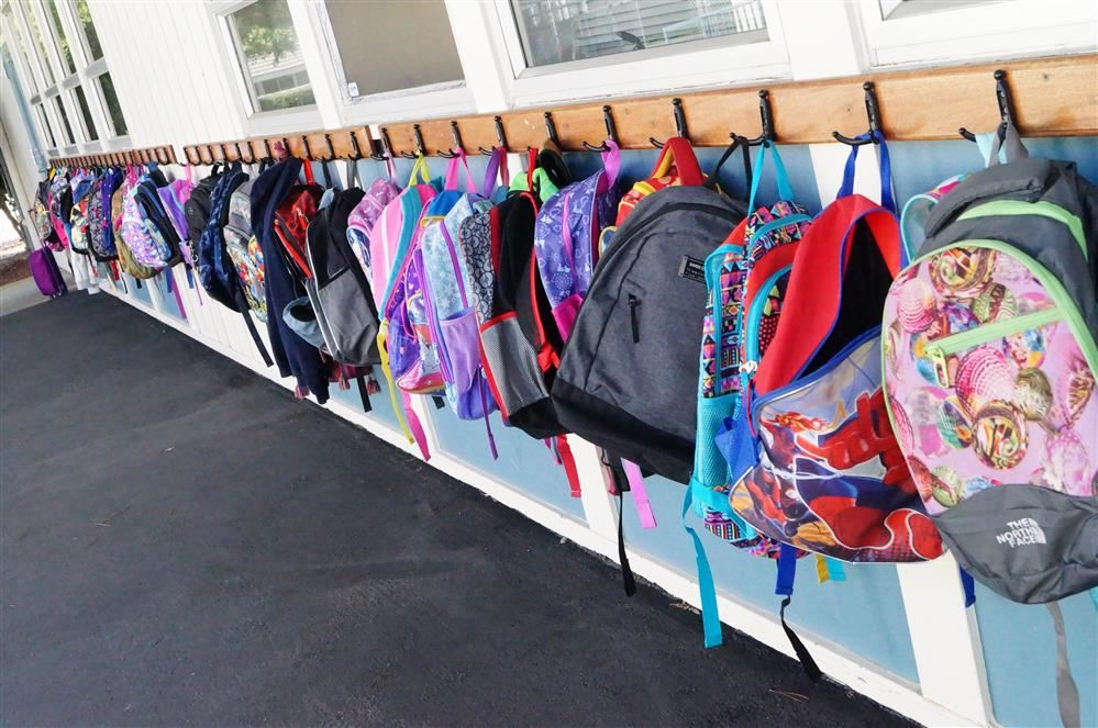 Backpacks lined up outside of a classroom door.