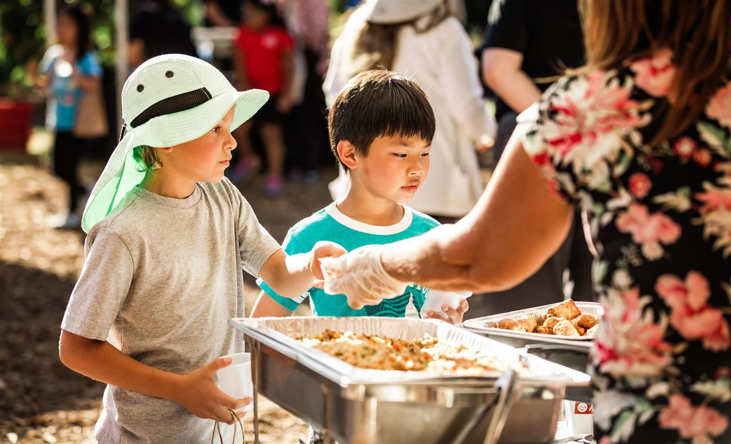 Children getting served food at tasting event
